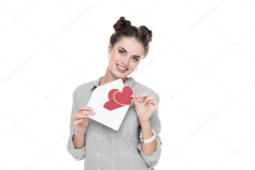smiling girl holding valentines postcard and envelope isolated on white