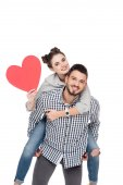 Fotografie boyfriend giving piggyback to girlfriend holding red heart isolated on white, valentines day concept