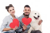 happy couple with samoyed dog and paper hearts isolated on white, valentines day concept