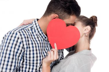 couple kissing and covering faces with paper heart isolated on white, valentines day concept