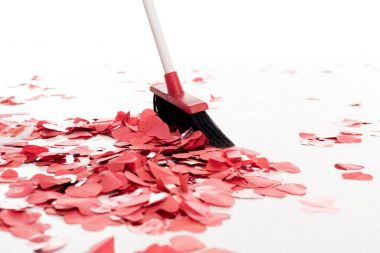 broom sweeping out heart shaped confetti isolated on white, valentines day concept