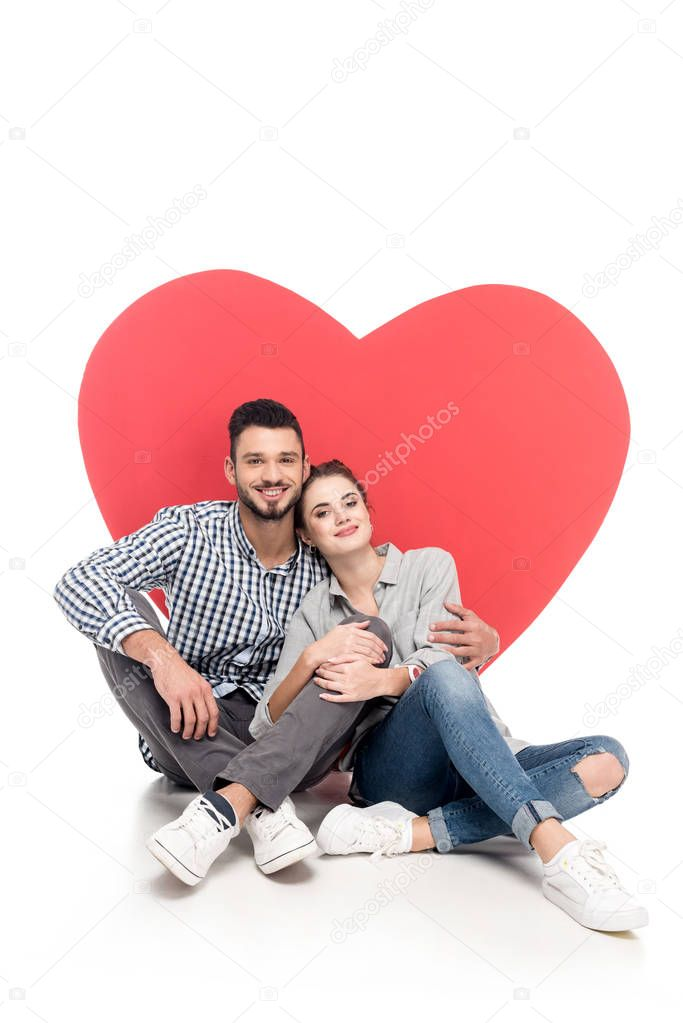 happy couple sitting near big heart on white, valentines day concept