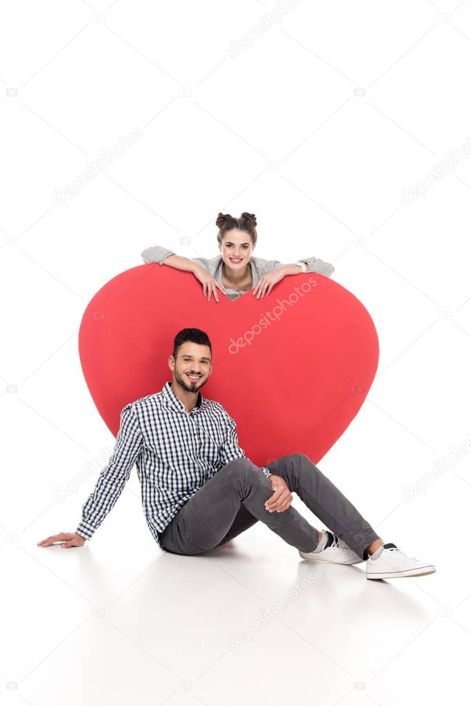 happy couple near big heart on white, valentines day concept