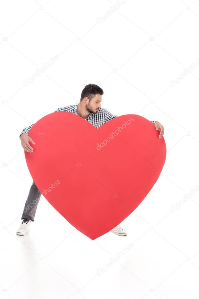 man trying to lift big heart on white, valentines day concept