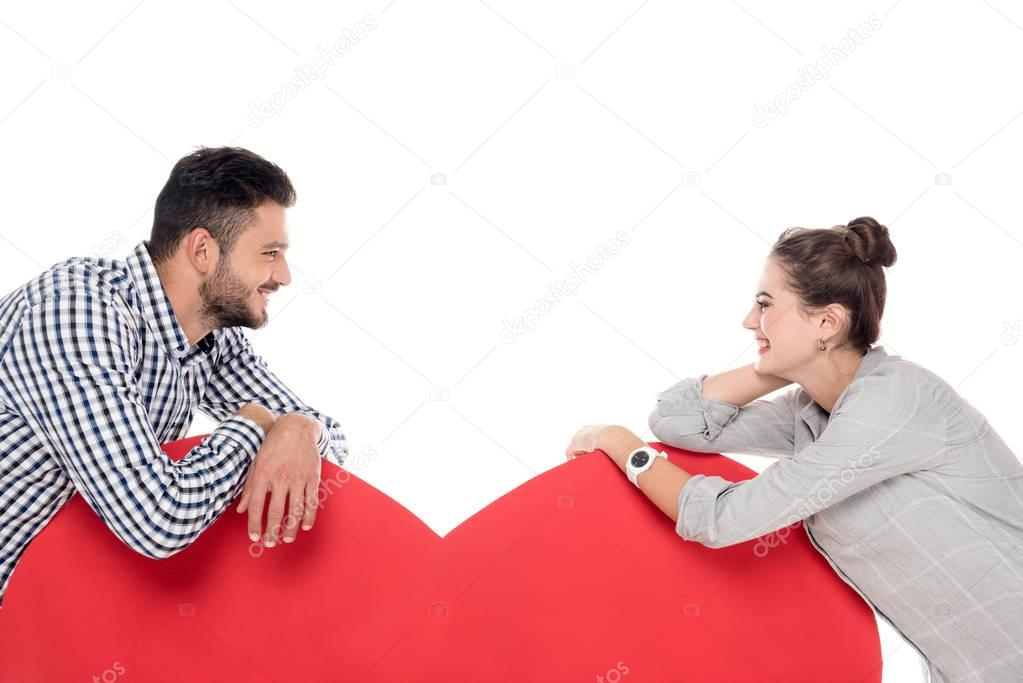 couple leaning on big heart isolated on white, valentines day concept