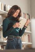 krásná dívka čtení knih v knihovně