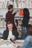 usmívající se studenti studující v knihovně s tabletů a notebooků