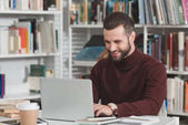 Fotografie usměvavý pohledný student pomocí přenosného počítače v knihovně