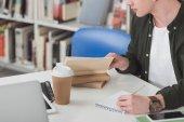Fotografia immagine potata di studente, libro di lettura e prendere appunti in biblioteca