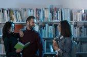 šťastná multikulturní studenty s knihami v knihovně