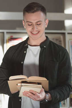 smiling handsome student standing and reading book in library