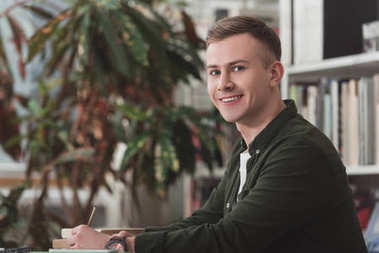 smiling male student sitting at table in library and looking at camera