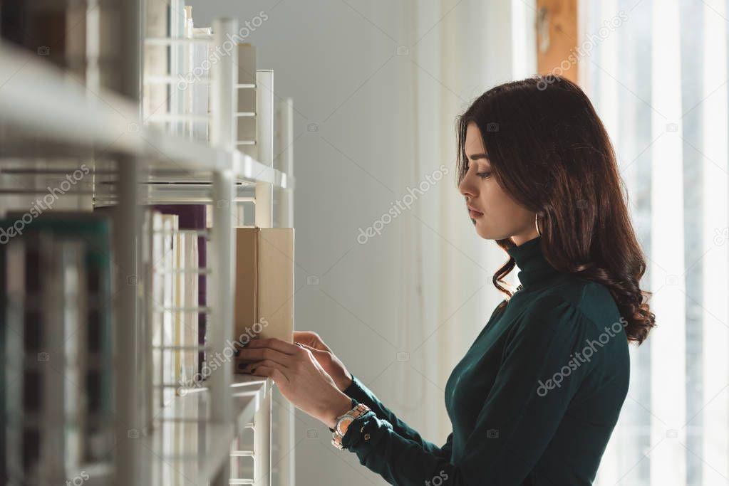 beautiful girl taking book from shelf