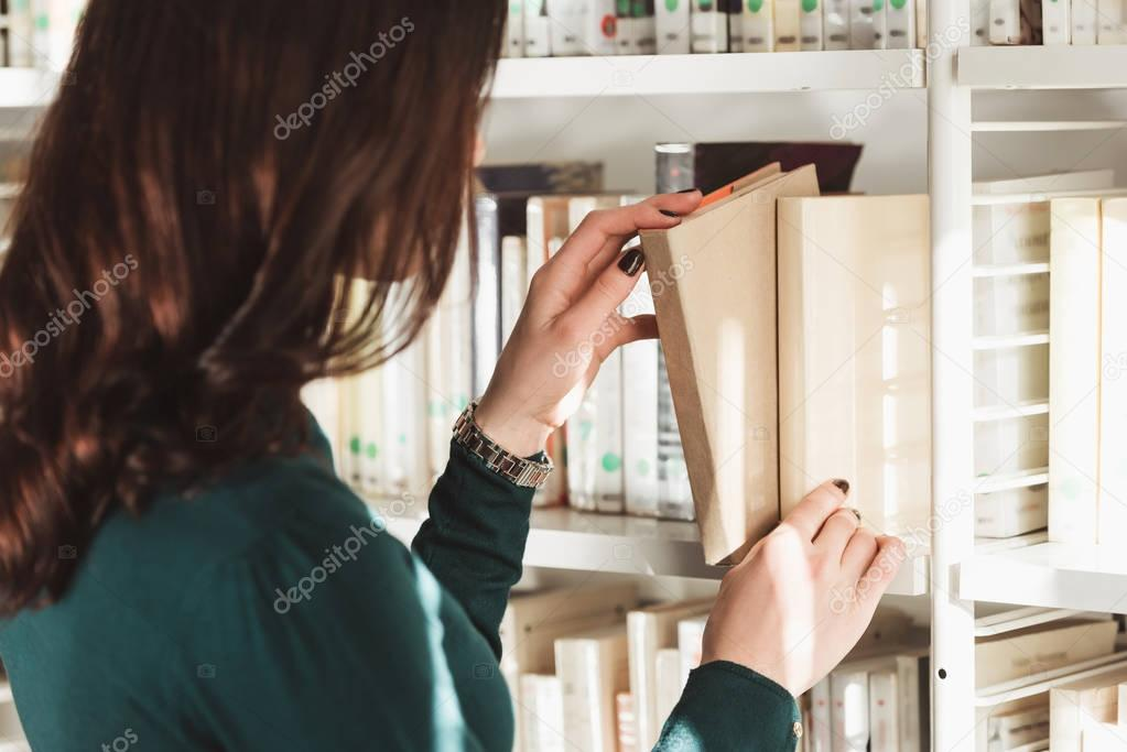 side view of student taking book from shelves in library