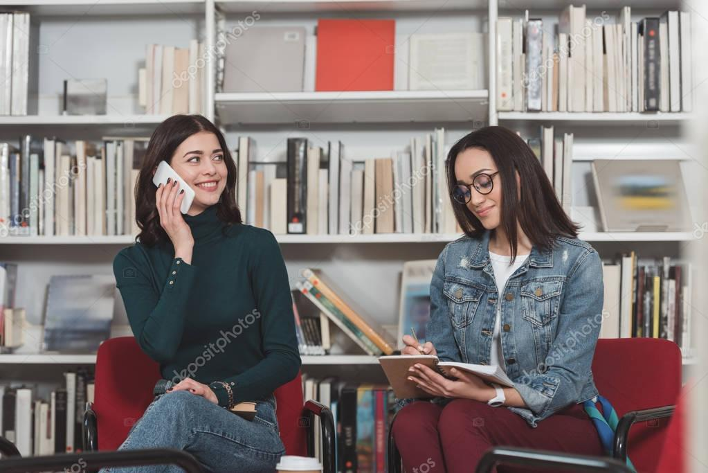 attractive student talking by smartphone in library
