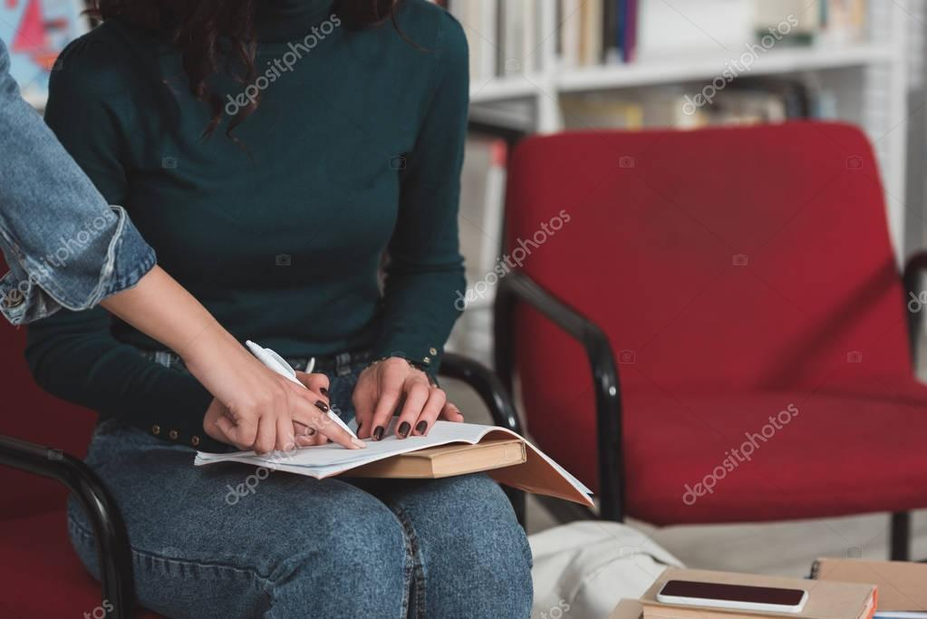 cropped image of girl pointing on something in friends notebook in library