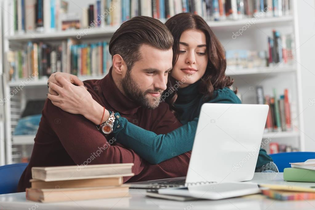 girlfriend hugging boyfriend and they looking at laptop in library