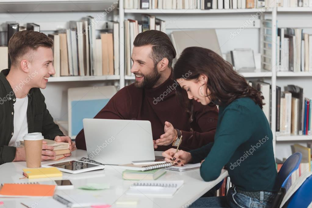 three students studying with laptop in library