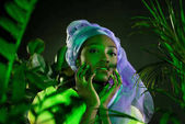 sensual african american woman in traditional wire head wrap under green light