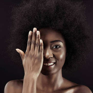 happy african american woman covering eye with hand isolated on black