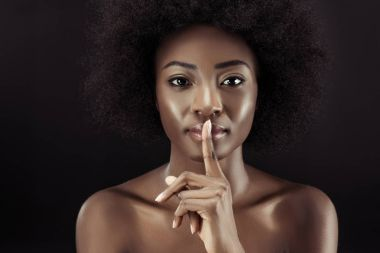 african american woman showing silence gesture isolated on black