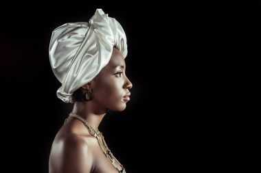 side view of african american woman in white wire head wrap isolated on black