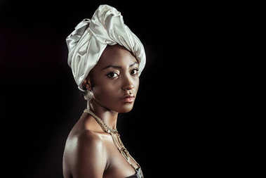 attractive african american woman in white wire head wrap isolated on black
