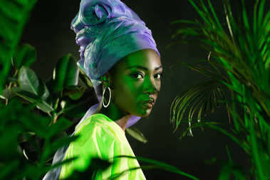 Attractive african american woman in traditional wire head wrap under green light behind leaves looking at camera stock vector