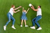 pohled z rodiny společně hrát volejbal na zeleném trávníku