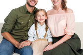 oříznutý snímek šťastná Dcera a rodiče na pohovce dohromady izolované na bílém