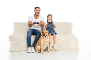 father and daughter playing video game with joysticks while dog sitting near, isolated on white