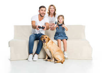 happy family playing video game with joysticks while dog sitting near, isolated on white