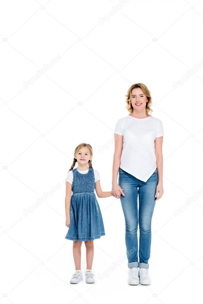 smiling mom and daughter holding hands, isolated on white