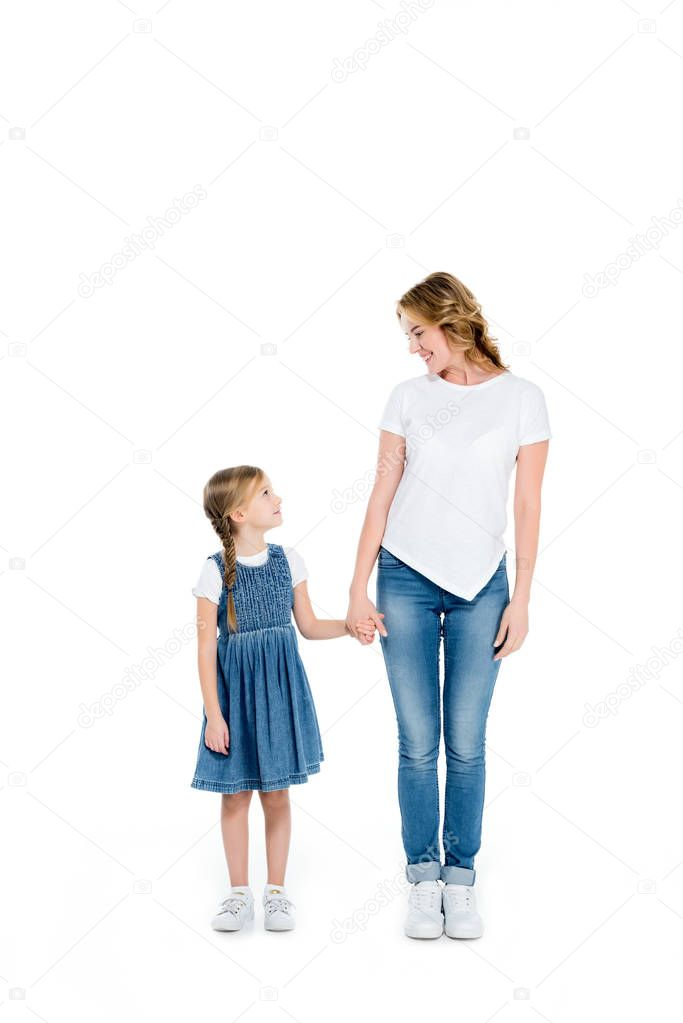 happy mother and daughter holding hands, isolated on white
