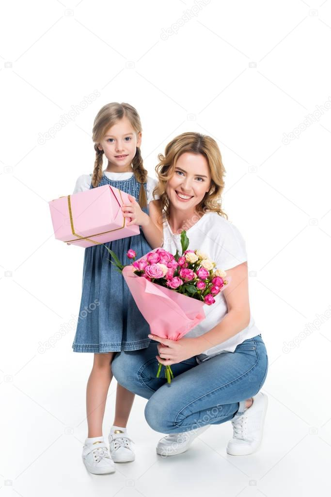 mother and daughter with gift and bouquet of flowers, isolated on white