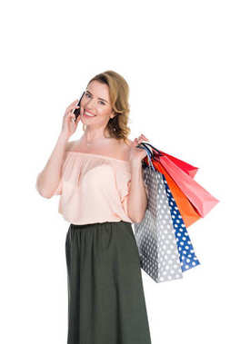 portrait of smiling woman with shopping bags talking on smartphone isolated on white