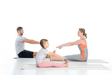 side view of parents and daughter in sportswear stretching on mats isolated on white