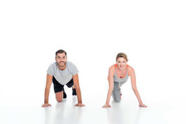 smiling sportive couple exercising together isolated on white