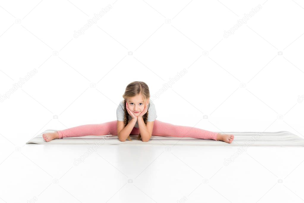 adorable child stretching on yoga mat isolated on white