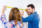 Photo girlfriend and boyfriend measuring wall with tape measure