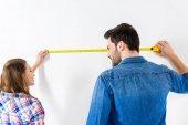 Fotografia fidanzata e fidanzato parete con misura di nastro di misurazione