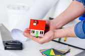 Fotografia ritagliate limmagine delluomo che tiene la piccola casa in mani