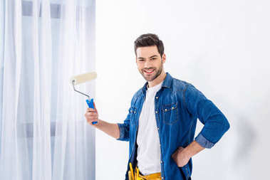 smiling man holding paint roll brush and looking at camera