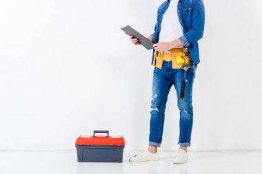cropped image of worker standing with clipboard near tools box