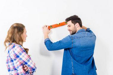rear view of boyfriend measuring wall flatness