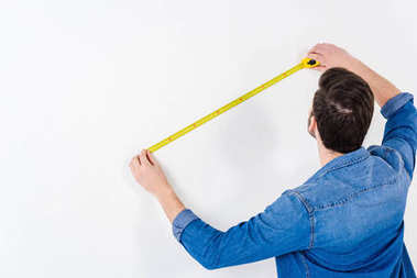 rear view of man measuring wall with tape measure on white