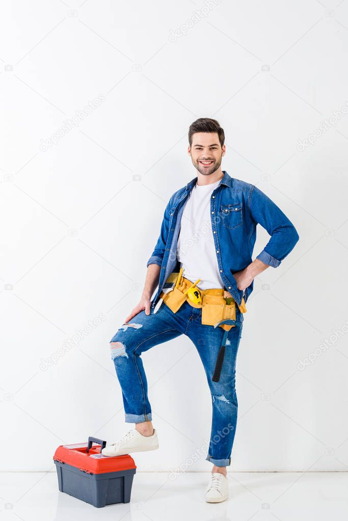 smiling worker putting leg on tools box and looking at camera
