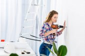 Fotografie side view of girl drilling wall