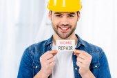 usměvavý pohledný muž drží domácí opravy karta