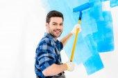 Fotografie usmívající se muž Malování zdi s modrou barvou